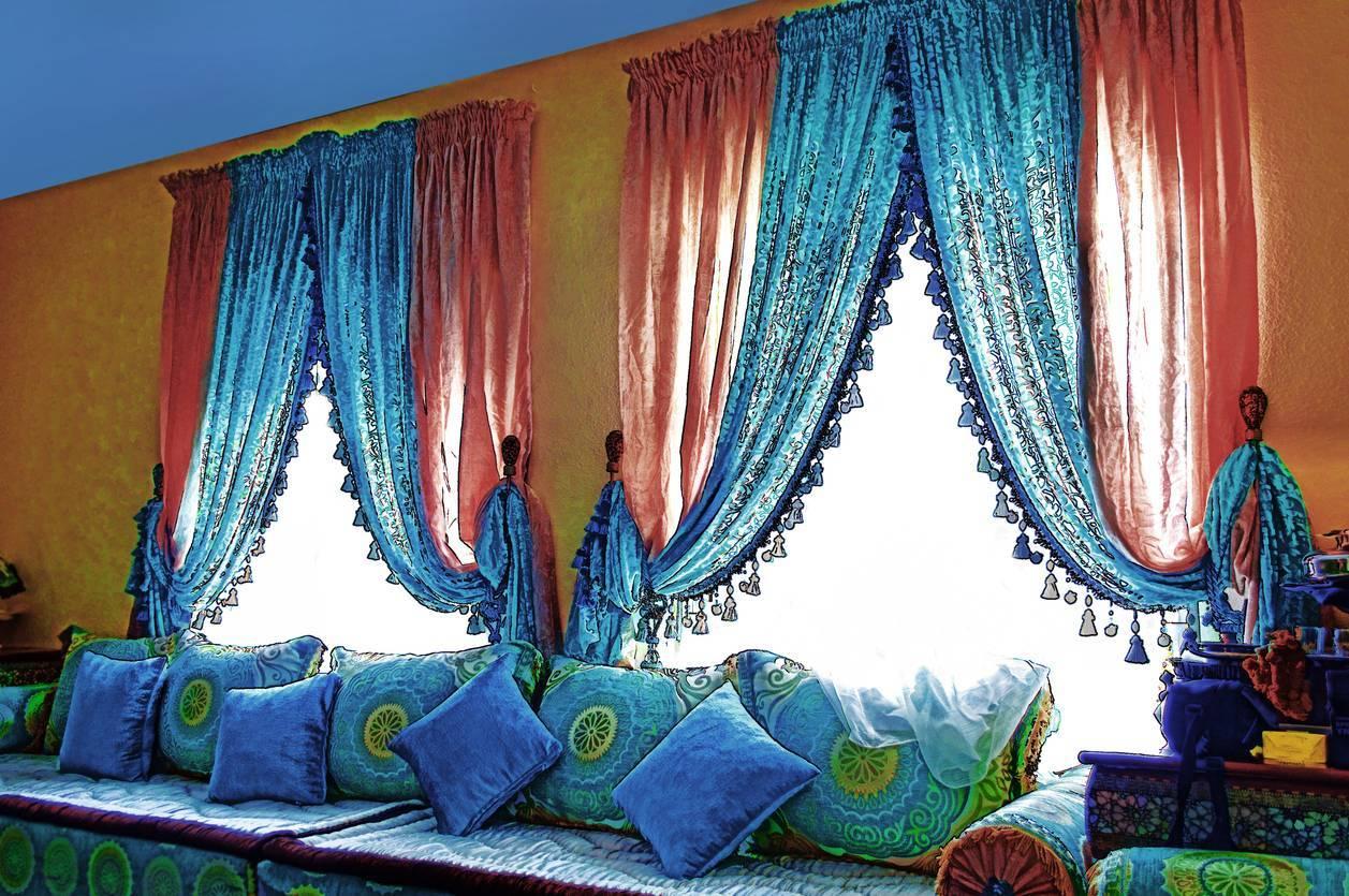 Salon décoré avec rideaux colorés, assises, tapis
